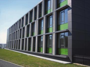 Horizontale, mit grünem Farbglas verkleidete Brüstungen werden überlagert durch großformatige, senkrechte Tafeln aus dunklem Faserzement.