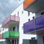 Balkone mit verschiedenfarbigen Glasbrüstungen an einer Wohnanlage in Riem.