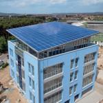Über dem Neubau scheint das Dach zu schweben als riesiges Sonnensegel aus Photovoltaikmodulen.