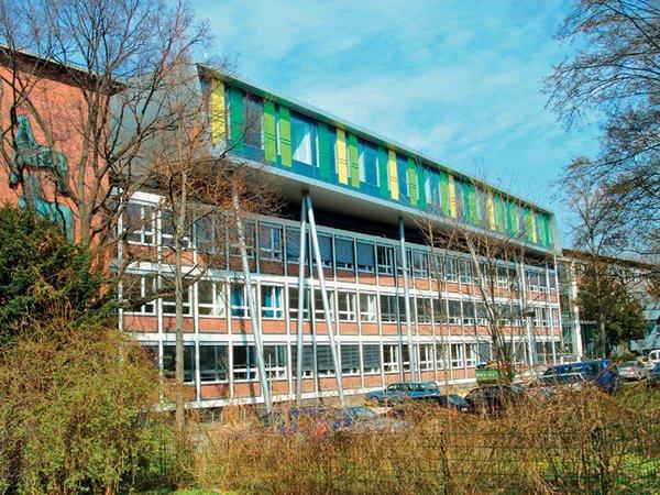 Aufgestockter Anbau aus Aluminium ragt aus der Fassade eines Klinkergebäudes.