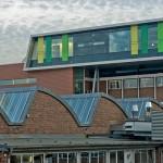 Passt sich die neue Ziegelfassade noch dem Bestand optisch an, so stehen Materialien und Farben des aufgestockten Bauteils im Kontrast dazu. Bild: Patrick Beuchert