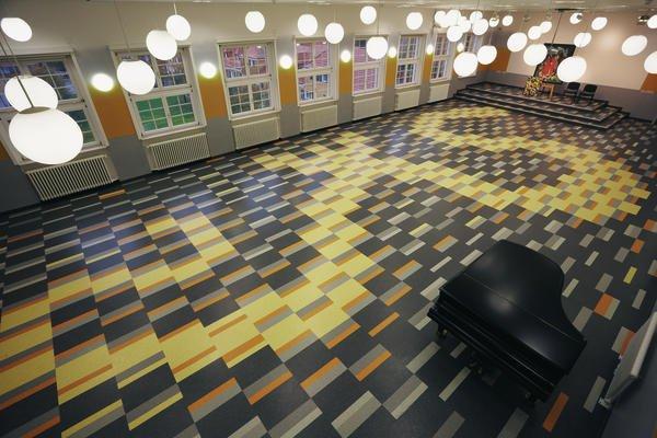 In der Schulaula wurde aus 1912 Kautschukbodenelementen eine imposante Raumintarsie geschaffen. Bild: Thomas Goos