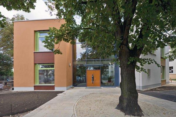 Das neue Gebäude besteht aus zwei massiven Baukörpern, in deren Mitte sich ein verglaster Eingangsbereich befindet.