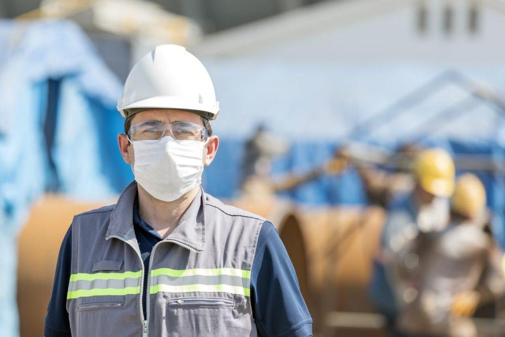 Bauarbeiter mit Corona-Schutzmaske auf Baustelle