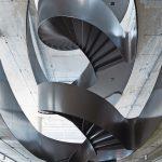 Spiralenförmig windet sich die Stahlwendeltreppe durch die Betonöffnungen nach oben. Bild: Noshe