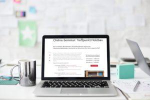 Laptop mit Online-Seminar zur Holzbauweise