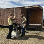 Die Ausstellungsbox und ihr neuer Besitzer: Schreinermeister Michael Kleinle (r.) lässt sich von René Görnhardt aus der Baufachinformation der FNR das Einfahren der Fassade für den Transport der Box erklären. Bild: FNR/K. Flotow