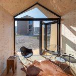 Der Innenraum wird dank Glas-Faltwand und dreieckiger Festverglasung lichtdurchflutet und optisch vergrößert. Bild: Solarlux