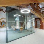 Im Dachgeschoss wurden sowohl die Holzkonstruktion des Dachstuhls freigelegt als auch zusätzliche Glasboxen eingesetzt. Es dient heute als multifunktioneller Open-Space-Raum für Seminare. Bild: Maciej Lulko