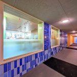 Für die Innenraumgestaltung kamen neben Holz und grauen Steinböden auch punktuell die für die Fassade verwendeten blauen und weißen Klinkerzum Einsatz. Bild: Michael van Oosten