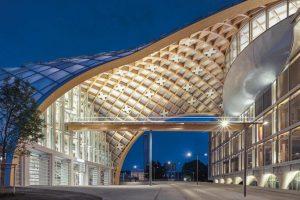 Brettschichtholz für gerade und unterschiedlich gekrümmte Träger verleimt zu einer gigantischen Holzgitterschale als Freiformkonstruktion. Bild: By Swatch