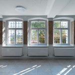 Flur mit vergitterten Holzfenstern und Heizkörpern