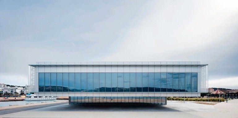 Verglastes Gebäude mit überkragendem zweiten Stockwerk