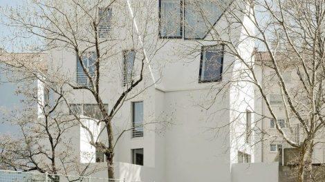 Nach dem Umbau: Mitten in Stuttgart wurde ein Gebäude doppelt aufgestockt und zu Wohnraum ausgebaut, Ansicht vom Pausenhof einer benachbarten Schule. Bild: Lignotrend | Brigida Gonzales, Stuttgart