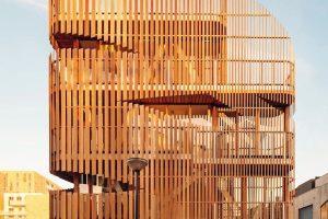 Zedernholz als Lamellenfassade vor geschosshoher Verglasung ermöglicht Tageslichteinfall im Doppelwohnhaus bei gleichzeitiger Privatsphäre. Bild: Francisco Nogueira