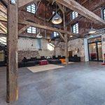 Loft mit freistehendem Dachgebälk, Hängelampen und unverputztem Klinker. Bild: Tölle Studios GmbH, Iserlohn