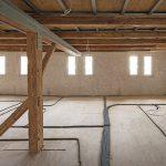 Raum mit Balkendecke und rohem Holzunterboden mit Kabelsträngen. Bild: David Franck