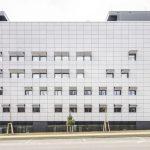 Mehrgeschossiges Gebäude mit weißen Fassadenplatten bei Tag. Bild: Colt International GmbH