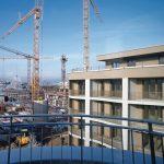Hausblock mit Stadtwohnungen im Vordergrund, Baustelle mit vier Kränen im Vordergrund. Bild: delaossaarchitekten