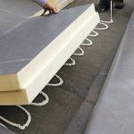 Eine Dämmplatte wird auf einem Flachdach verlegt. Bild: puren