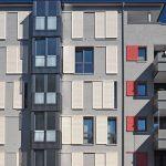 Fassade eines Wohngebäudes mit grauem Außenputz und mattfarbigen Aluminium-Schiebeläden und -balkonen
