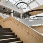 Atrium mit Treppenaufgang und großen, kreisförmigen Designleuchten. Bild: Erne AG Holzbau | Raumwerk & Spreen Architekten AG | Thomas Koculak