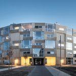 Lebendig strukturierte Holz-Glasfassade – vom begrünten Innenhof aus und bei Abendstimmung gesehen. Bild: Rasmus Hjortshoj