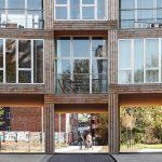Geschwungene Fassade zur Straße hin mit Durchwegung zum Innenhof: Rhythmischer Kontrast der großen Glasflächen zu den in Holz ausgeführten Fassadenverkleidungen. Bild: Rasmus Hjortshoj