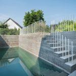 Der Pool mit Gegenstromanlage wird oberhalb der Wasserfläche von traditionell hergestellten Stampfbetonwänden eingefasst. Bild: Gui Rebelo / rundzwei Architekten