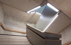 """Der Sichtbeton im Treppenhaus wird u. a. durch den integrierten Lichtkanal """"fino"""" beleuchtet. Bild: Lichtwerk"""