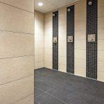 An den Wänden der Gemeinschaftsduschen betonen vertikal verlaufende Streifen aus Mosaik (5 x 5 cm) den Bereich der Duscharmaturen. Bild: Rako