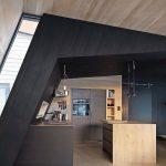 Offene Küchenecke, gekennzeichnet durch die überkragende Wand- und Deckenkonstruktion aus schwarz lackierter Fichte. Bild: Invit Arkitekter, Ålesund / Johan Holmquist