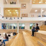 Im gebäudehohen, glasüberdeckten Atrium befinden sich Cafeteria, Bibliothek und ein kleiner Filmsaal. Zentrales Element ist die breite Holztreppe. Bild: Sónia Arrepia