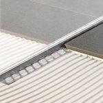 Perforationsfrei in den Fliesenbelag integrierbares Profil zur Aufnahme einer Glastrennwand. Hier ist das Profil zusätzlich keilförmig aufgebaut, um auch das Gefälle zum normalen Bodenniveau sauber abzuschließen. Bild: Blanke