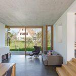 Zu den weißen Wänden und einzelnen Akzenten in Sichtbeton kombinierte Innenarchitektin Katrin Holzer helle Eichenmöbel. Die Fenster- und Türrahmen sind ebenfalls aus Holz. Bild: Zooey Braun