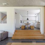 Wie viele Häuser aus den 20er-Jahren hat auch das Einfamilienhaus in Stuttgart-Degerloch ein etwas erhöhtes Erdgeschoss. Zum neuen Wohn-/Esszimmer im ebenerdigen Anbau führt daher eine flache Sitztreppe von der alten Küche hinunter. Bild: Zooey Braun