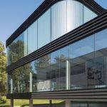 Gerade und gekrümmte Glaselemente bilden zusammen mit schwarzen Aluminiumbändern die geschwungene Glasfassade. Bild: Luuk Kramer