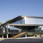 Modernes zweistöckiges Gebäude auf Stelzenunterbau mit umlaufender, raumhoher Glasfront. Bild: Luuk Kramer