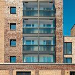 Die Kombination aus Brüstung und beweglichen Glaselementen schützt vor Schall und lässt sich flexibel öffnen und schließen. Bild: Solarlux GmbH