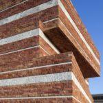 Gestapelte und geschichtete Natursteinfassaden aus rotem Travertin und weißem Architekturbeton. Bild: ScagliolaBrakkee / © Neutelings Riedijk Architects