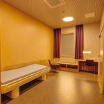 Ein Patientenzimmer im therapeutisch-orangefarbenen Licht für die Nachtstunden. Alle Leuchten sind sicher in Wände oder Decken eingelassen. Bild: Glamox