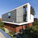 Das weiß verputzte Obergeschoss verbindet die grünen Schieferflächen mit den Fassadenteilen aus rostbraunen Cortenstahl. Bild: Rathscheck Schiefer