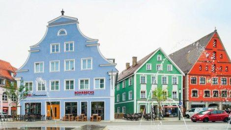 Bunte Hausfassaden in einer Innenstadt mit Springbrunnen im Vordergrund