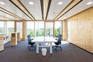 Büroraum mit großer Fensterfläche, Teppichboden und Naturholzverkleidung
