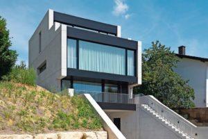 Steinblöcke, grüner Hang und Glas-Beton-Haus.