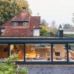 Durchgängig verglaster Wohn- und Essbereich mit offener Küche, in Souterrainbauweise