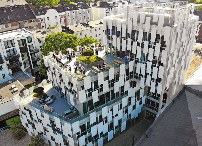 mehrstöckiges Bürogebäude mit begrünten Dachterrassen und Glasfassade mit Sonnenschutzpanels