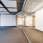 Büro mit einseitger Glaswand hin zum Flur, Teppichboden & Sichtbetondecke mit Deckensegeln