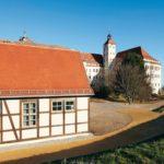 geweißter Fachwerkbau, im Hintergrund Schlossturm
