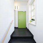 Flur einer Arztpraxis mit Stufen, weiß mit grüner Tür